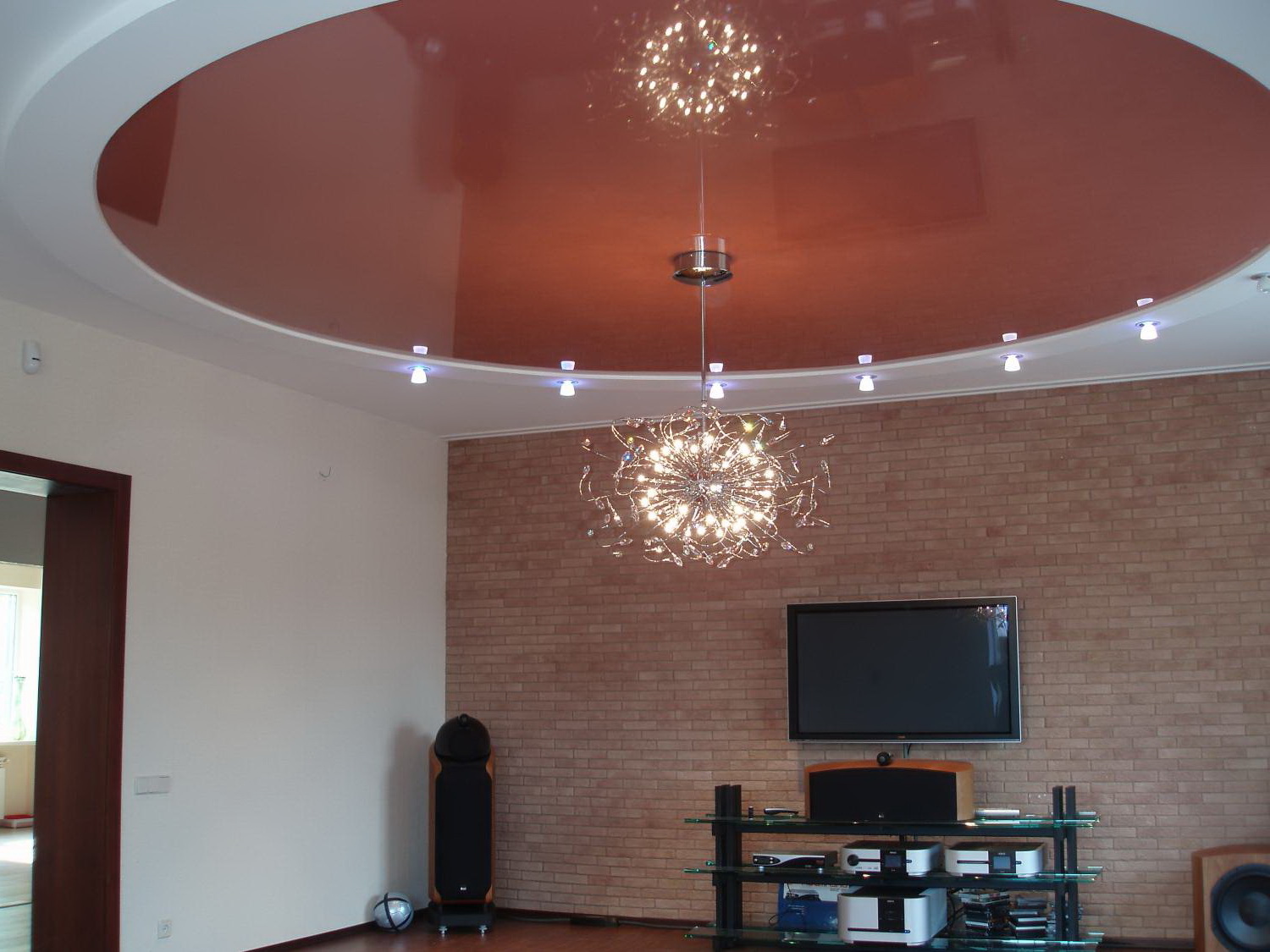 Stretch ceiling in the design of the living room with a pendant lamp