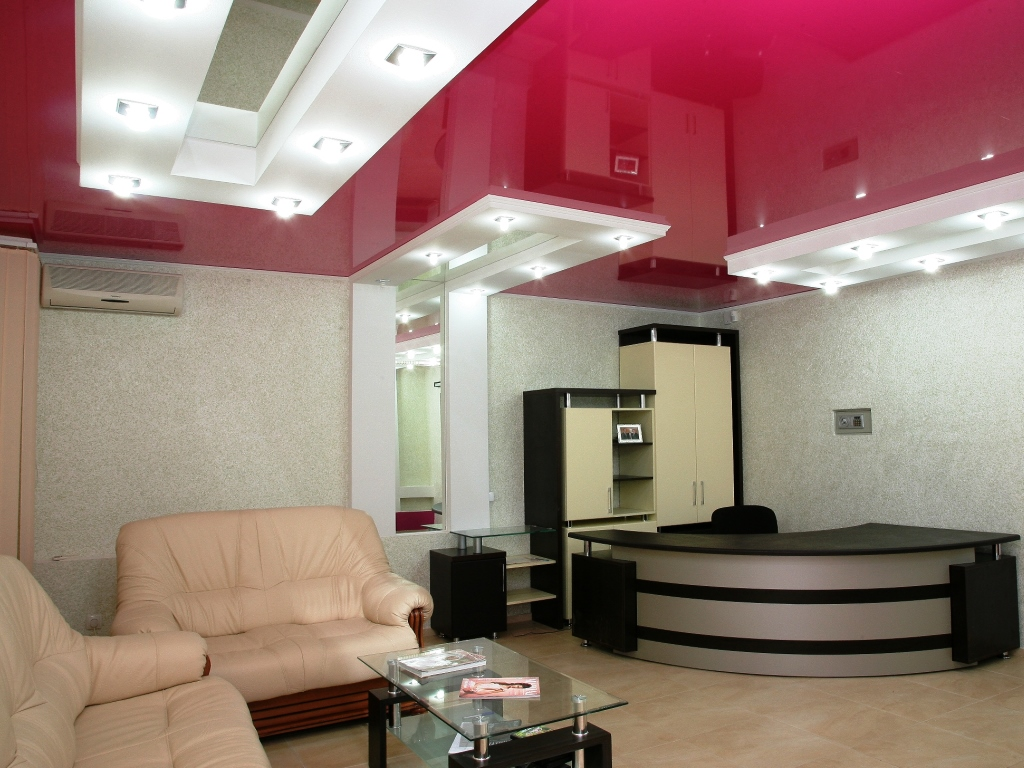 Pluses of a stretch ceiling of red color with white inserts for a large living room