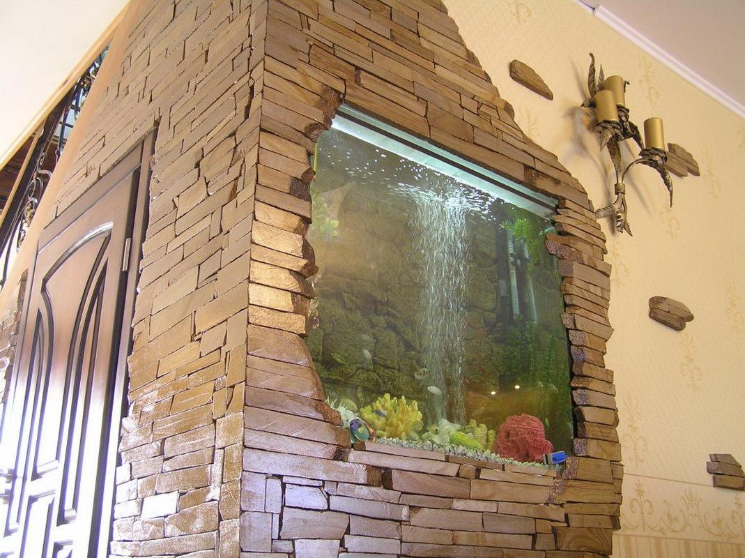 Aquarium dans le mur du couloir, bordé de pierre