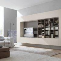 Grāmatu plaukti un televizors pie sienas viesistabā