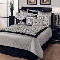 Black bed with a white blanket in the bedroom of a city apartment