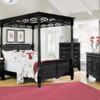 Black bed with a hoodie in a bright bedroom