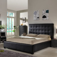 Black bed and gray-white walls in the bedroom