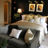 Black wall above the head of a dark bed