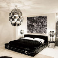 Black bed with white pillows in a light gray room