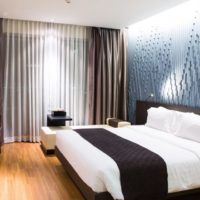 Bright lighting in the bedroom with a dark bed