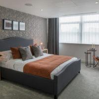 Gray bedroom and orange bedspread