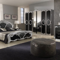 Glossy facades of wardrobes in a classic bedroom