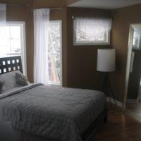 Gray bedspread and dark brown bedroom walls