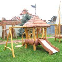 Mājiņā no koka izveidots rotaļu laukums