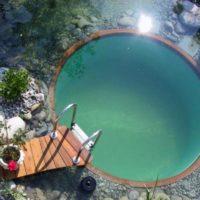 Apaļš baseins ar koka tiltu