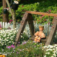 Dekoratīvas šūpoles dārza noformējumā