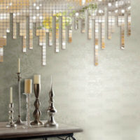 Spoguļa mozaīka uz sienas un svečturi uz galda