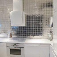 Spoguļmozaīkas un baltas fasādes mūsdienīgā virtuvē