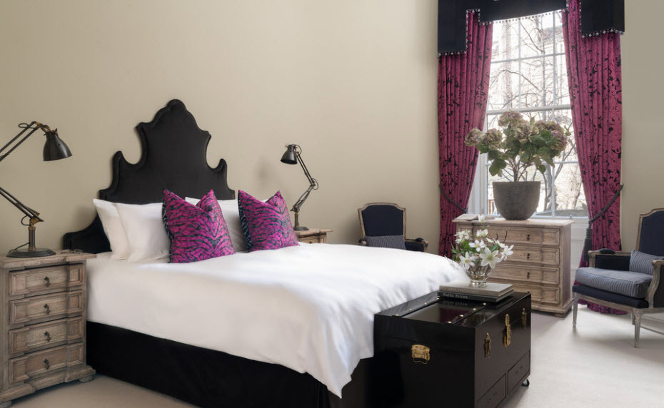 White bedspread on a black bed and pillows in lilac covers
