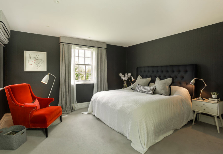 White hoodie on a black bed in a bedroom with gray walls