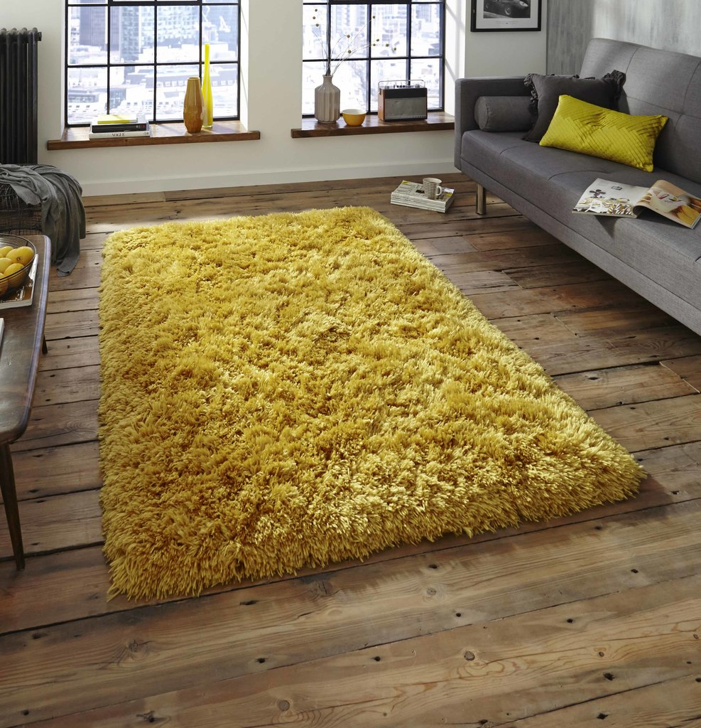 Yellow rug on a wooden floor in a dark bedroom
