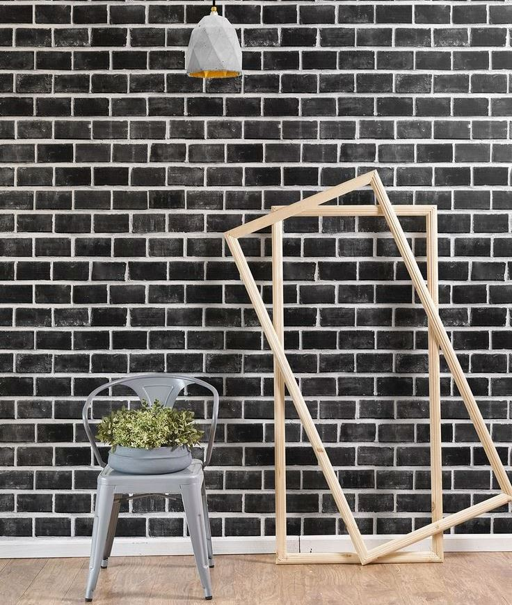 Wooden frames near the wall with black brick wallpaper