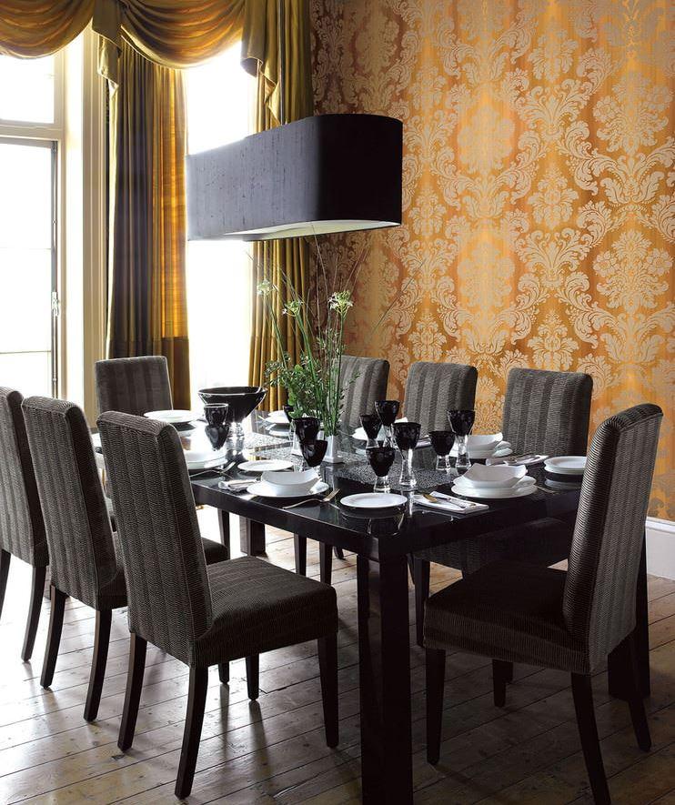 Crne stolice za trpezarijskim stolom u sobi s tamnim zlatnim tapetama
