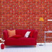 Red sofa on brickwork background