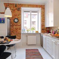 Brick accent in the interior of the white kitchen