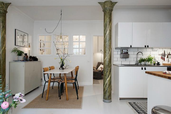 Skandināvu stila virtuves-viesistabas interjers ar marmora kolonnu