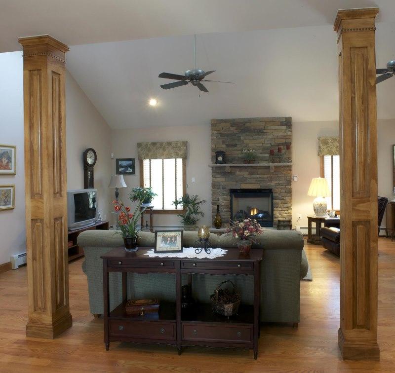 Koka kolonnas viesistabas interjerā