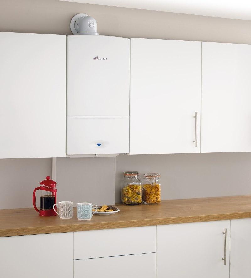 Intérieur de cuisine avec chaudière à gaz blanche entre les armoires de cuisine