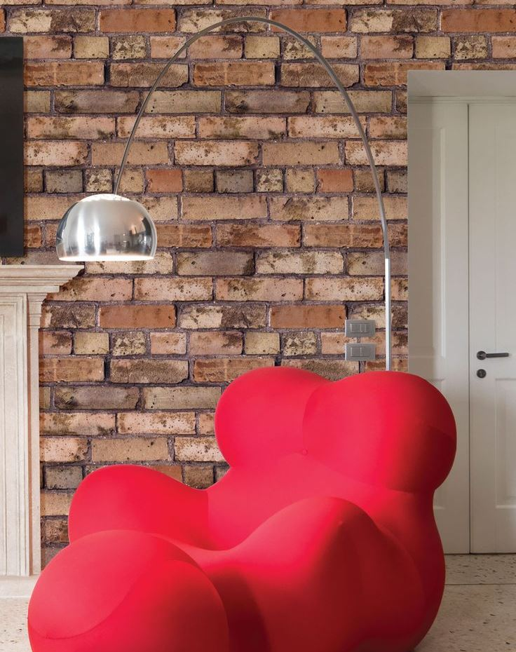 Fancy red armchair against a brick wall