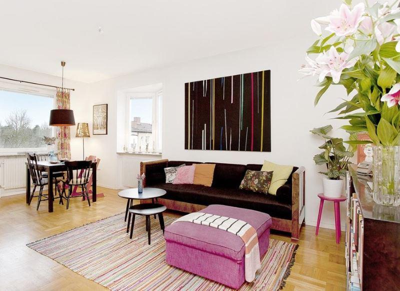 Dzīvojamās istabas interjers baltā krāsā ar aveņu pufu