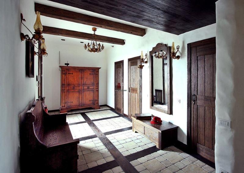 Tērzētavas ieejas zāle ar tumšām koka durvīm