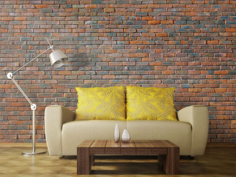 Cream upholstered sofa in front of a brick wall