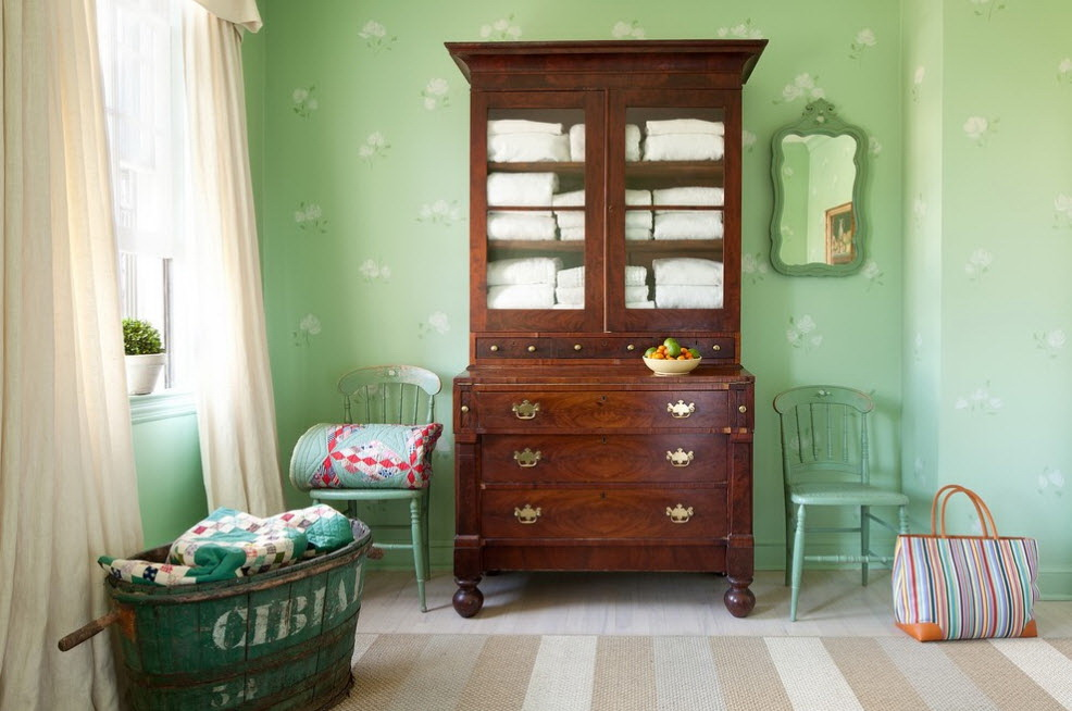 Brown chest of drawers on a background of green wallpaper