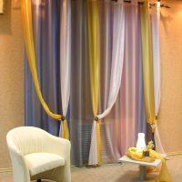Aizkari no daudzkrāsaina tilla uz viesistabas loga
