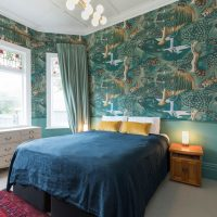 Turquoise wallpaper in the bedroom of a city apartment