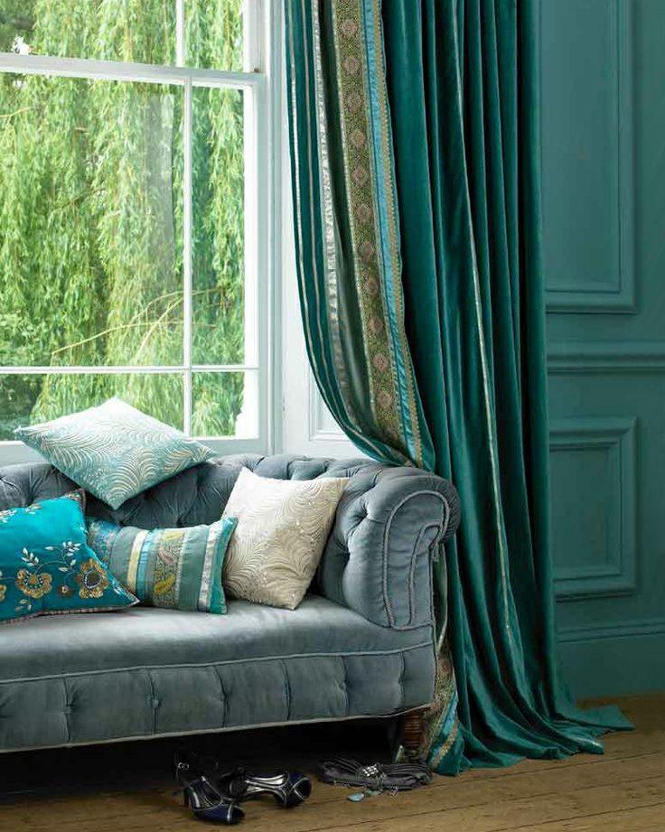 Dīvāns viesistabas loga priekšā ar smaragda aizkariem