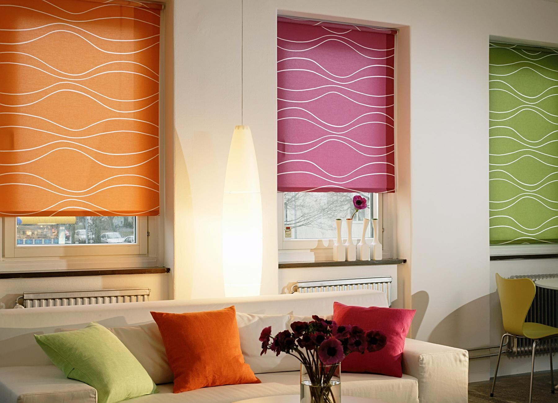 Trīs logi ar dažādu krāsu rullo žalūzijām