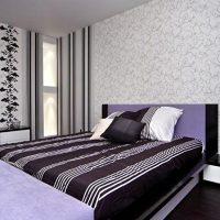 Couvre-lit rayé dans la chambre à coucher avec deux types de papier peint