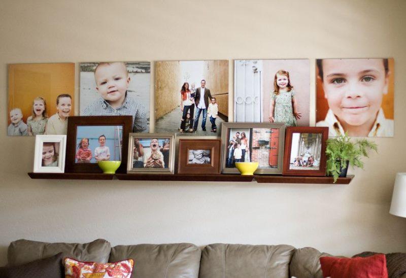 Plaukts ar ģimenes fotogrāfijām uz viesistabas sienas