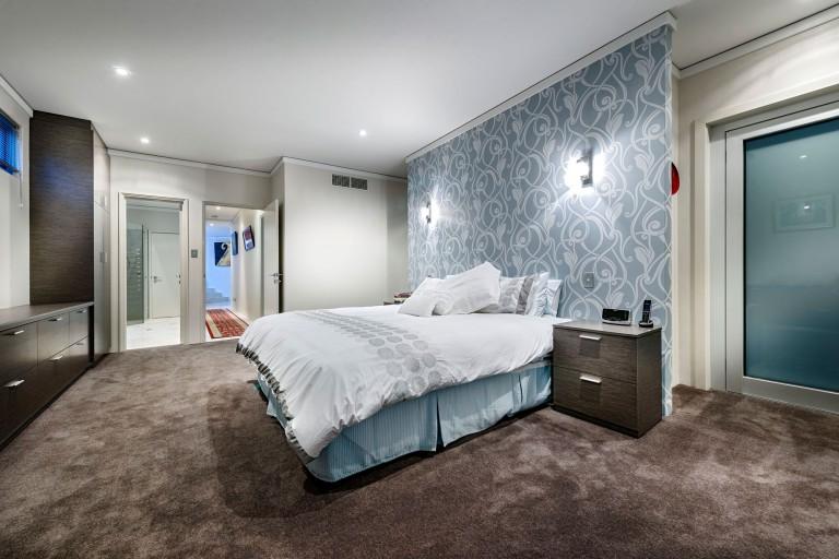 Sol de la chambre tacheté avec papier peint sur le mur.