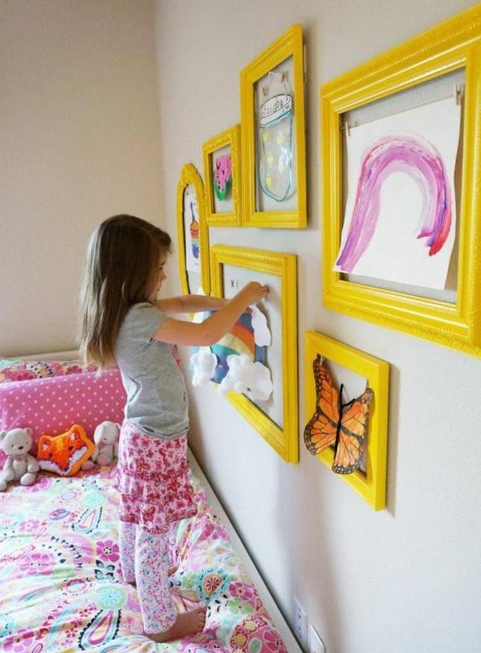 Meitene rotā istabu ar saviem zīmējumiem.
