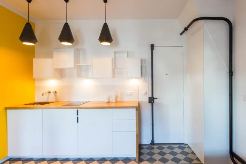 Black pipes in the interior of a white kitchen