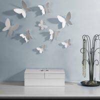 Papillons de papier blanc sur un mur bleu