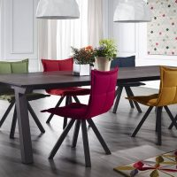 Chaises rembourrées de différentes couleurs dans la salle à manger-cuisine d'une maison privée