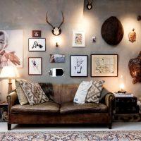 Vecs dīvāns pie pelēkās sienas ar fotogrāfijām