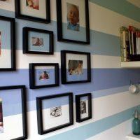 Melni rāmji un foto uz svītrainās sienas.