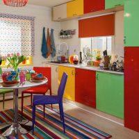 Svītrains paklājs virtuvē ar krāsainām fasādēm.