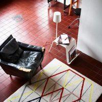 Svītrains paklājs uz keramikas grīdas