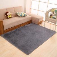 Pelēks paklājs uz krēmkrāsas grīdas