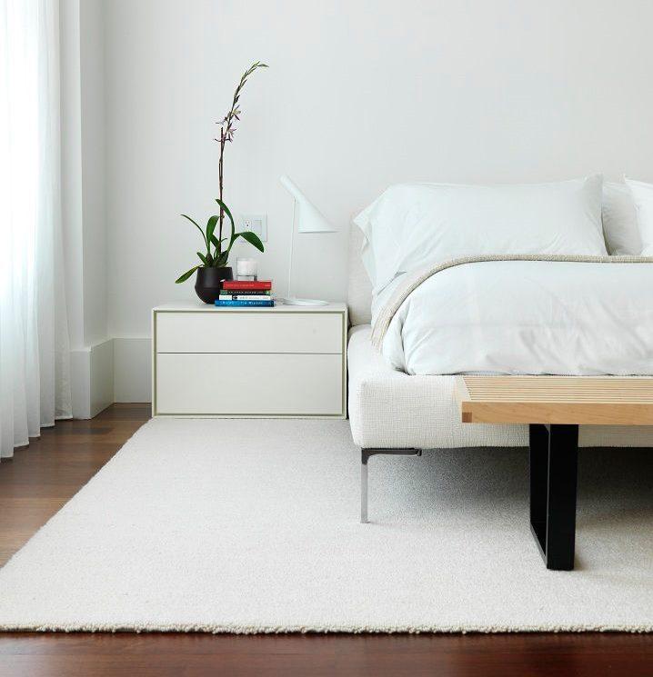 Minimālisma balts paklājs guļamistabas grīdā